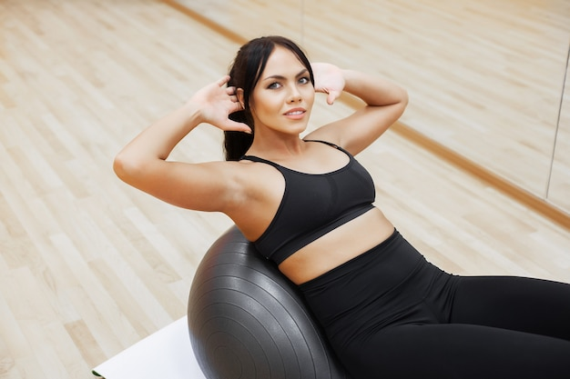 Mujer fitness mujer atractiva joven que hace ejercicios usando bola
