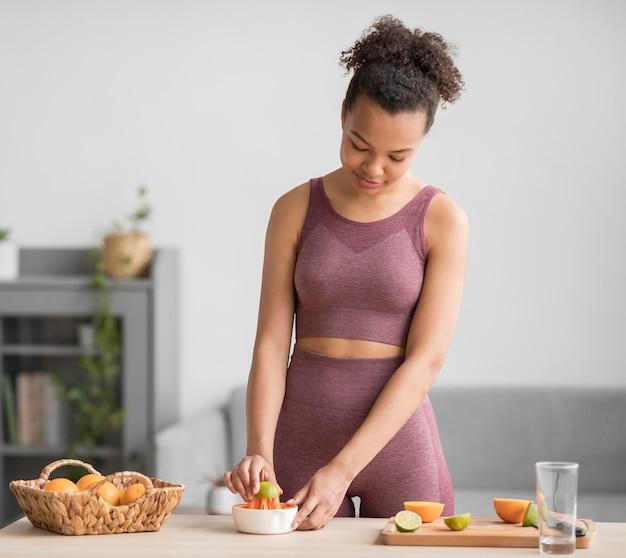 Mujer fitness preparando un jugo de fruta saludable