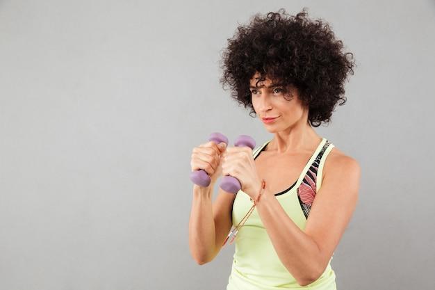 Mujer de fitness rizado concentrado haciendo ejercicio con pesas