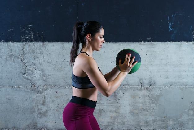 Mujer fitness sosteniendo balón medicinal y ejercicio en el gimnasio