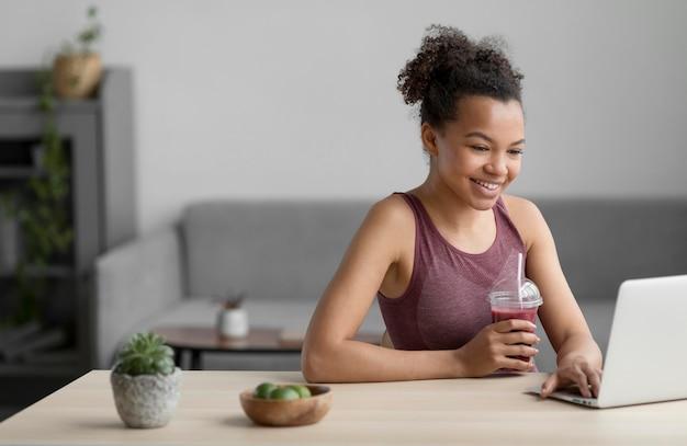 Mujer fitness tomando un jugo de fruta mientras usa una computadora portátil