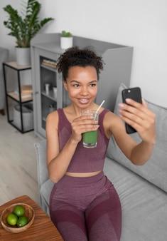 Mujer fitness tomando un selfie mientras toma un jugo de frutas
