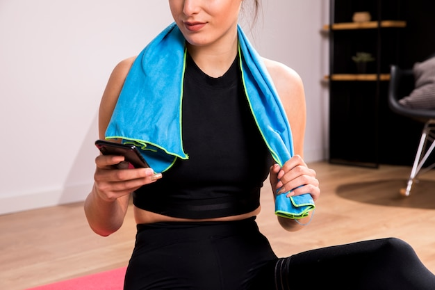 Mujer fitness usando el teléfono móvil
