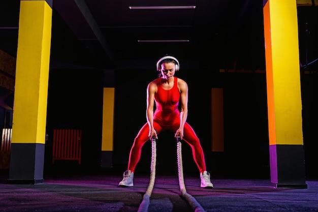 Mujer fitness utilizando cuerdas de entrenamiento para hacer ejercicio en el gimnasio. atleta trabajando con cuerdas de batalla en el gimnasio de cross