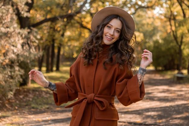 Mujer flaca sonriente elegante atractiva con el pelo rizado caminando en el parque vestida con abrigo marrón cálido, estilo callejero de moda de otoño