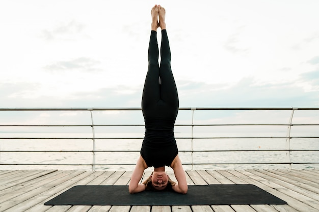 Mujer flexible practicando yoga y de pie sobre su cabeza en asana cerca del mar al amanecer de la mañana, haciendo ejercicios de deporte y fitness
