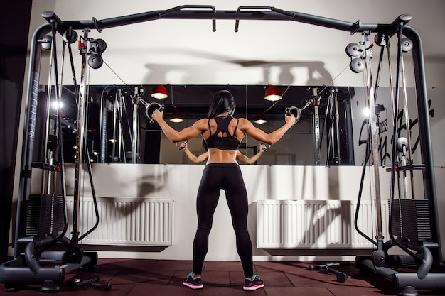 Mujer flexionando los músculos en la máquina de cable en el gimnasio