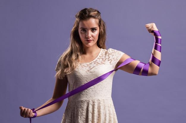 Mujer flexionando su brazo con cinta como un signo de fuerza