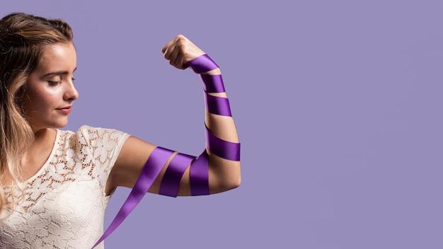 Mujer flexionando su brazo con cinta y copia espacio