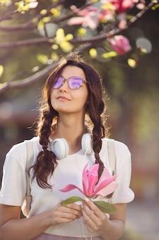 Mujer con flor al aire libre en el parque de la ciudad