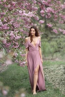 Mujer en el floreciente árbol de sakura en la naturaleza