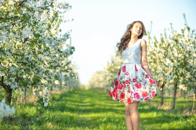 Mujer en un floreciente jardín de cerezos en primavera