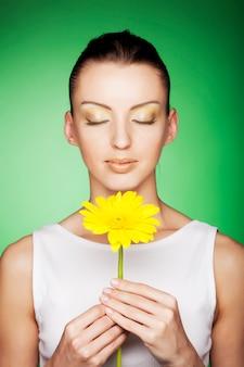 Mujer con flores amarillas en verde