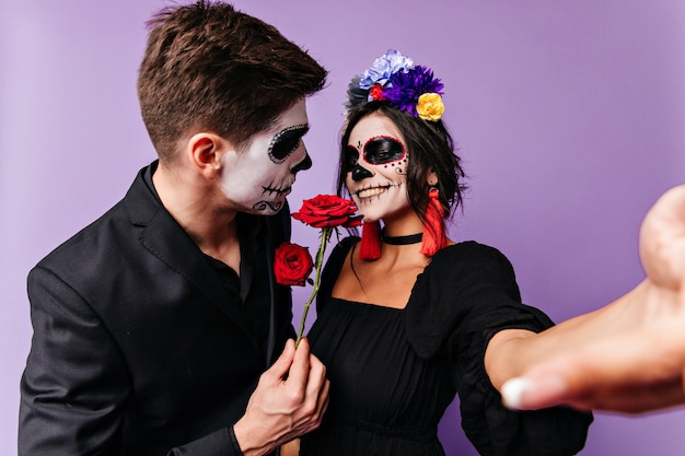 Mujer con flores azules en el pelo toma selfie y sonríe, recibiendo como regalo rosa roja de su novio. retrato de pareja de enamorados con maquillaje de halloween posando sobre fondo púrpura.