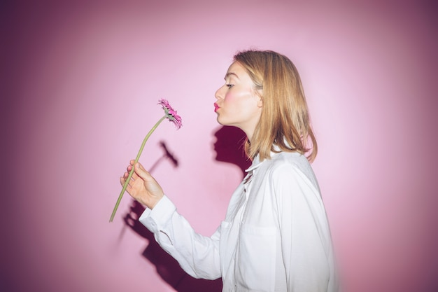 Mujer con flores gerbera haciendo pucheros en los labios.