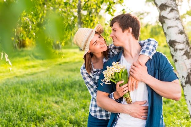 Mujer con flores de nuevo abrazando hombre guapo