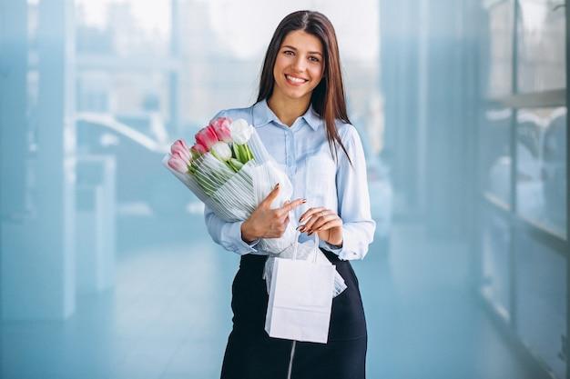 Mujer con flores en una sala de exposición de coches