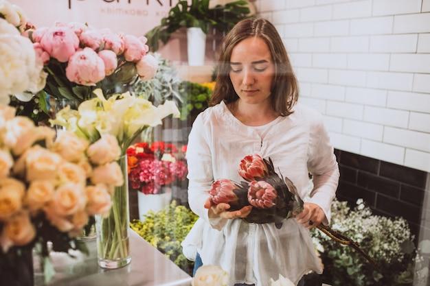 Mujer florista en su propia tienda de flores cuidando flores