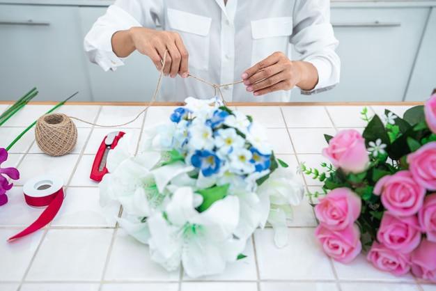Mujer floristería organizando flores artificiales