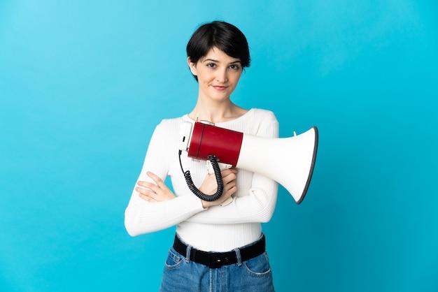 Mujer con fondo aislado de pelo corto sosteniendo un megáfono y sonriendo