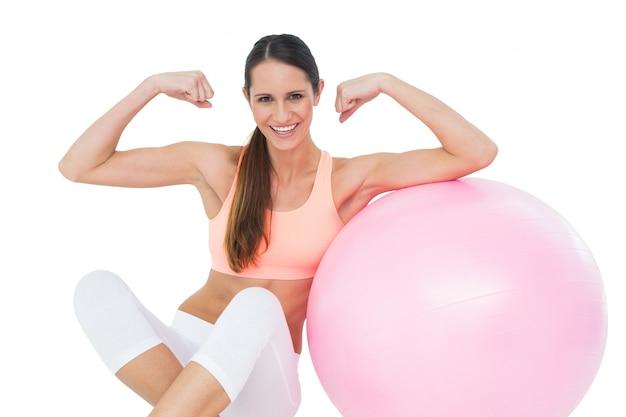 Mujer en forma alegre que dobla los músculos por la bola de la aptitud