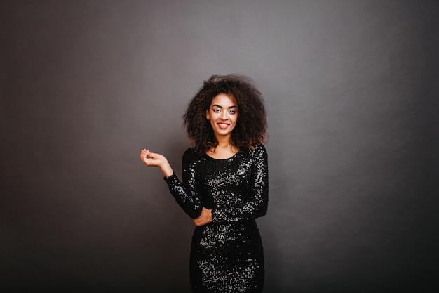 Mujer en forma bien vestida con cabello ondulado sonriendo al frente