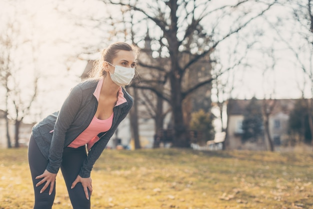 Mujer en forma durante la crisis de covid-19 que tiene descanso de correr