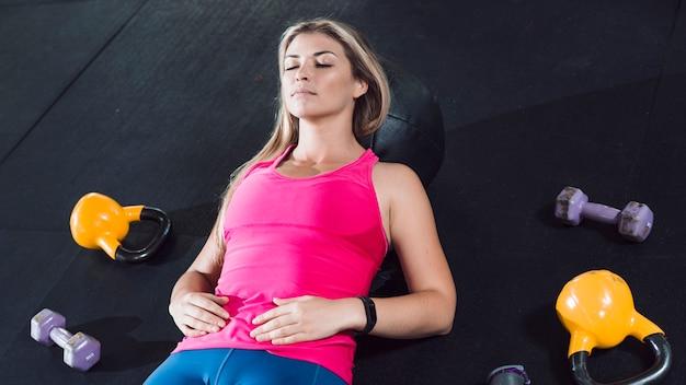Mujer en forma descansando en el piso cerca de equipos de ejercicio