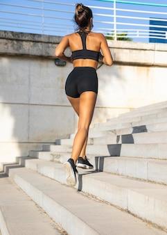 Mujer en forma de disparo completo corriendo en las escaleras