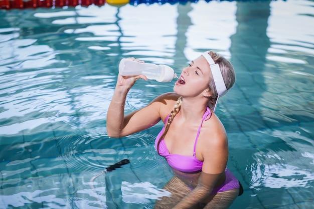 Mujer en forma haciendo bicicleta submarina y agua potable en la piscina