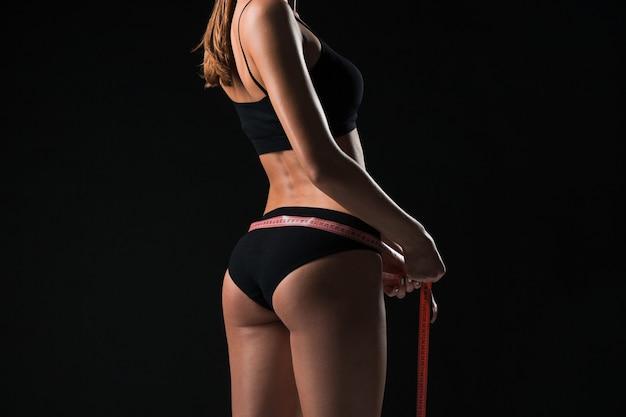 La mujer en forma mide la forma perfecta de hermosa figura. estilos de vida saludables y concepto de fitness