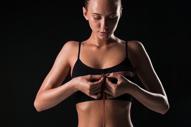 La mujer en forma que mide la forma perfecta del cuerpo hermoso. concepto de estilos de vida saludables