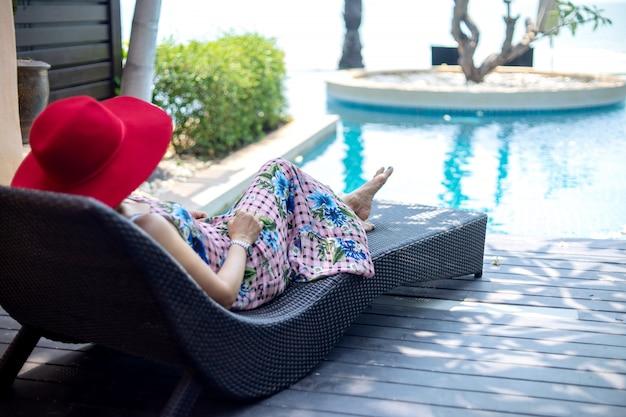 La mujer de la forma de vida del verano con el sombrero rojo pone en sunbed cerca de piscina.