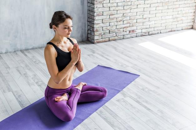 Mujer fortaleciendo su espalda en una postura de loto