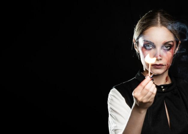 Mujer con fósforo encendido y espacio de copia