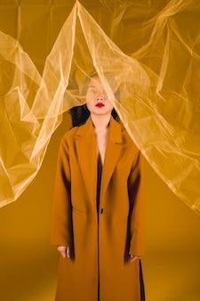 Mujer fotogénica en abrigo amarillo.
