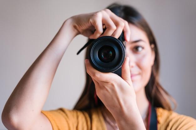 Mujer fotógrafa en casa usando una cámara réflex