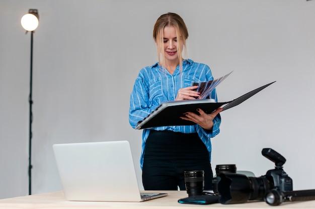 Mujer fotógrafa navegando por un álbum de fotos