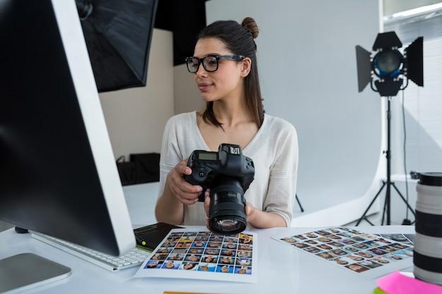 Mujer fotógrafa revisando fotos capturadas en su cámara digital