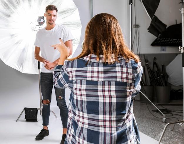 Mujer fotógrafa tomando una foto de modelo masculino