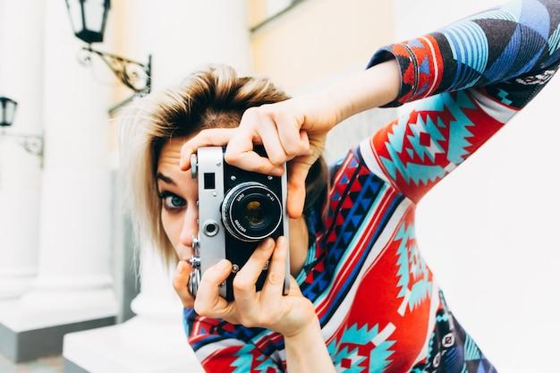 Mujer fotografiada cámara retro en la ciudad