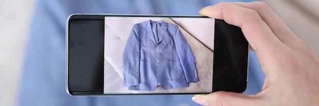 Mujer fotografiando chaqueta azul en el teléfono con cámara closeup venta de cosas viejas concepto