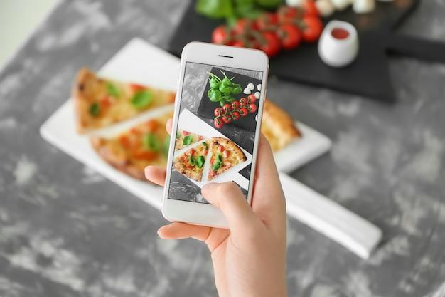 Mujer fotografiando deliciosa pizza margherita con teléfono móvil