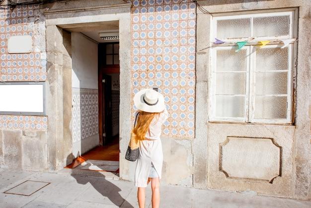 Mujer fotografiando la fachada del edificio antiguo con azulejos portugueses en porto, portugal
