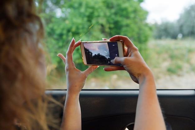 Mujer fotografiando la naturaleza en el teléfono inteligente