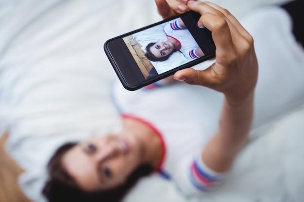Mujer fotografiando a sí misma en el teléfono móvil
