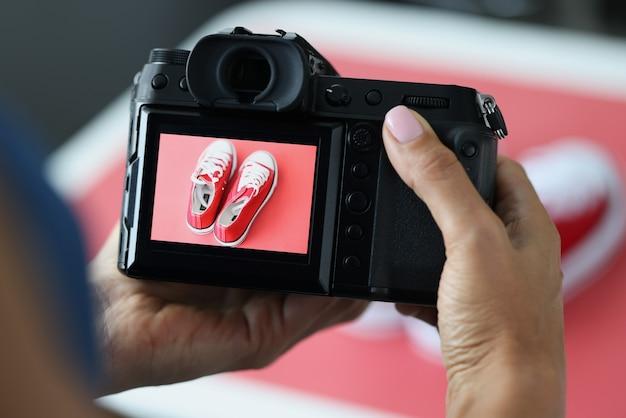 Mujer fotografiando zapatos deportivos rojos en primer plano de cámara profesional