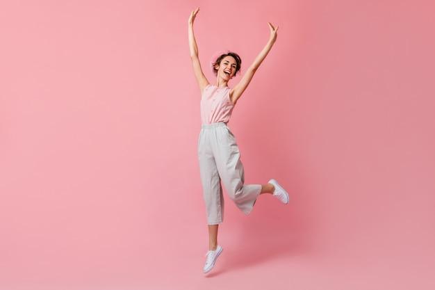 Mujer francesa alegre en pantalones saltando con las manos arriba