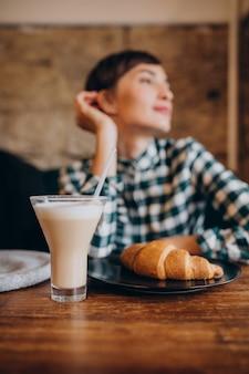 Mujer francesa en café bebiendo café con leche y comiendo croissant