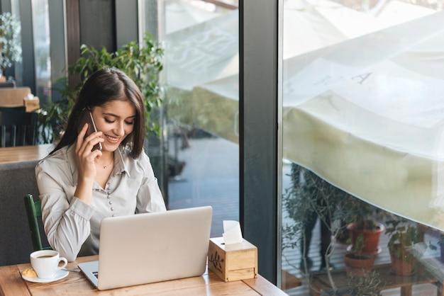 Mujer freelance trabajando con portátil en cafetería